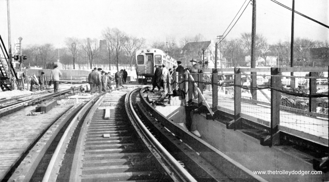 "This is one of the very first CTA trains to use the permanent routing into the DesPlaines terminal on March 20, 1960. This bridge, originally designed for three tracks, is still in use. But with expressway construction far from finished, note the grade crossing right behind the bridge. That implies that the bridge was built first and then the area around it was later cleared out for the highway. Cars today go underneath the ""L"". Behind the train, you can see a handsome 1939 field house, still in use today in a nearby park."